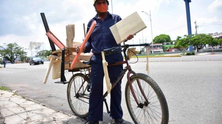 Se gana la vida vendiendo artesanías de madera sobre dos ruedas